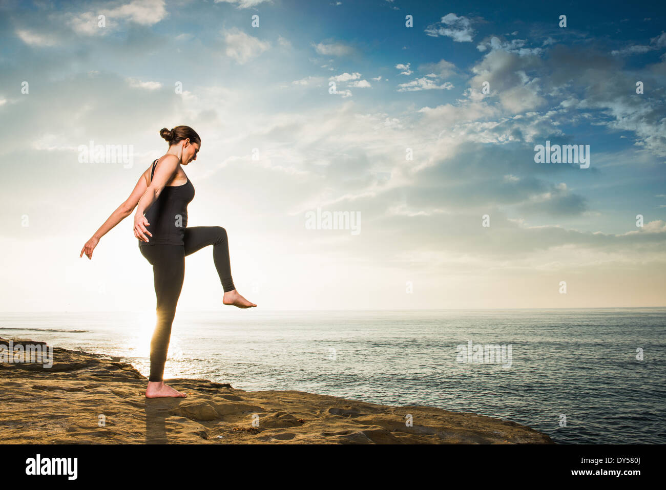 Women on cliff, in yoga position - Stock Image