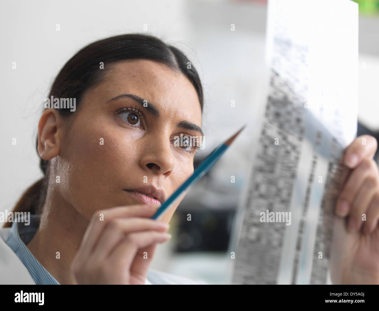 Female scientist examining DNA gel in laboratory for genetic research - Stock Image