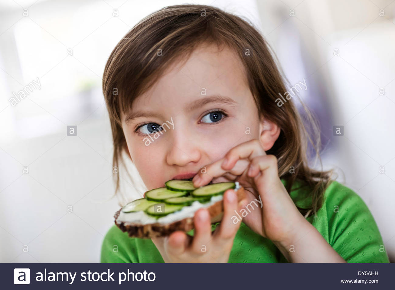 Girl eating a cheese and cucumber open sandwich - Stock Image