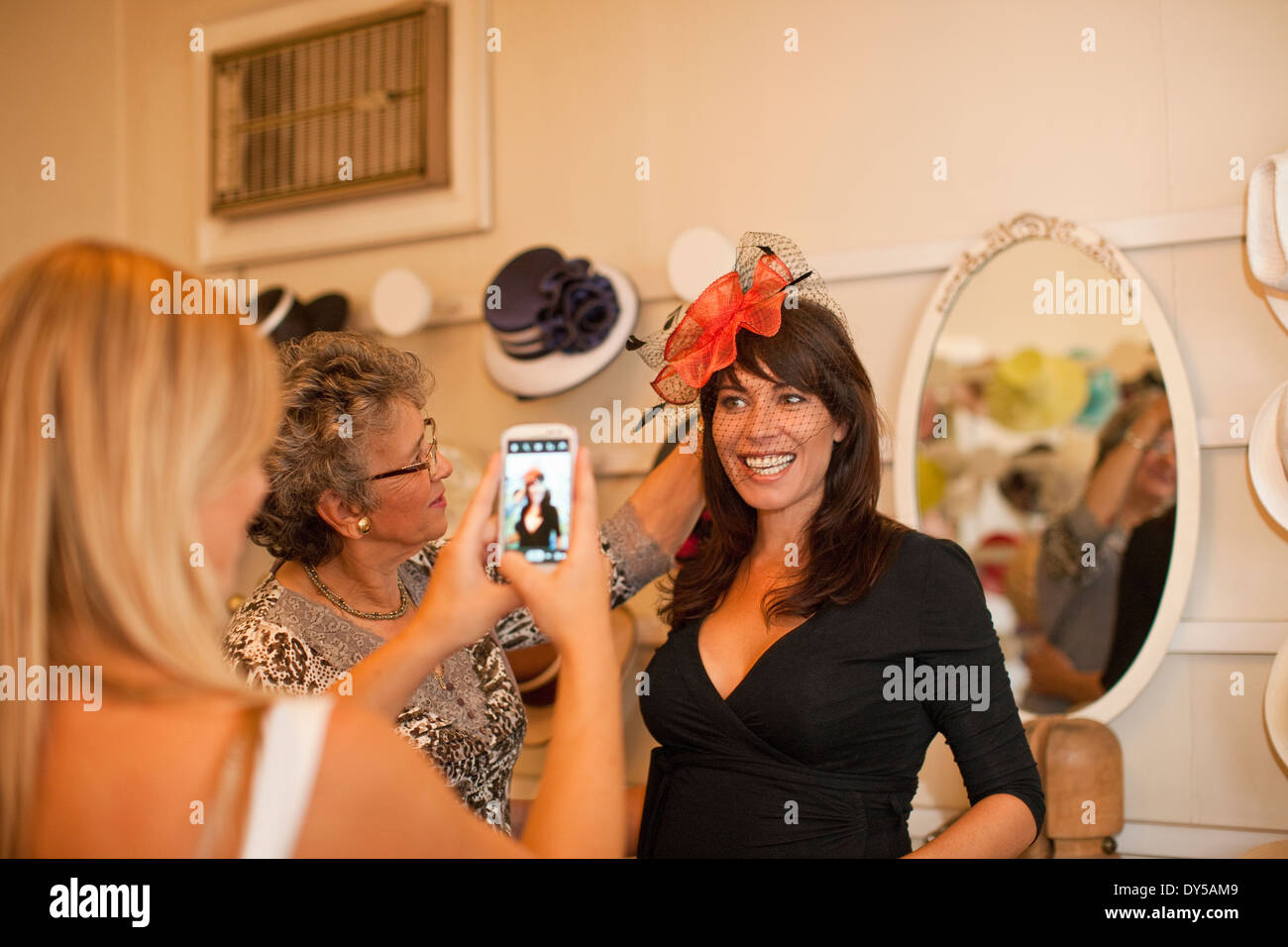 Woman being photographed in traditional milliners shop - Stock Image