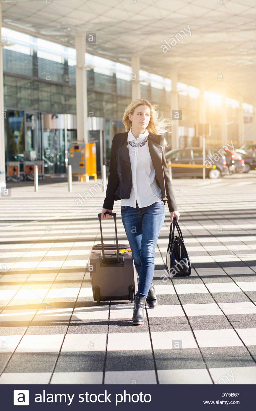 Young woman walking outside airport, pulling wheeled suitcase - Stock Image