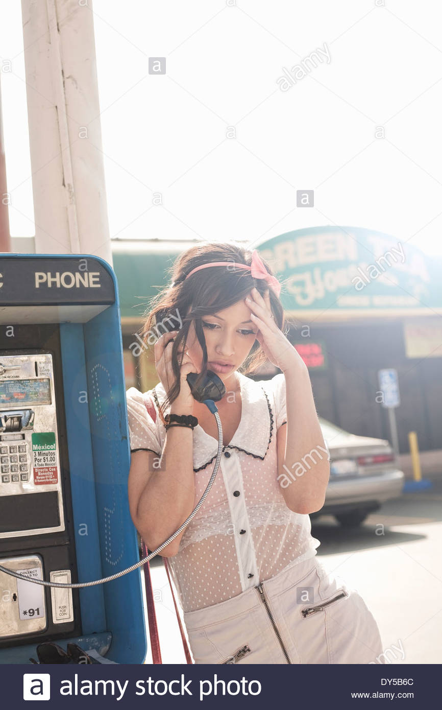 Unhappy young woman talking on telephone booth phone - Stock Image