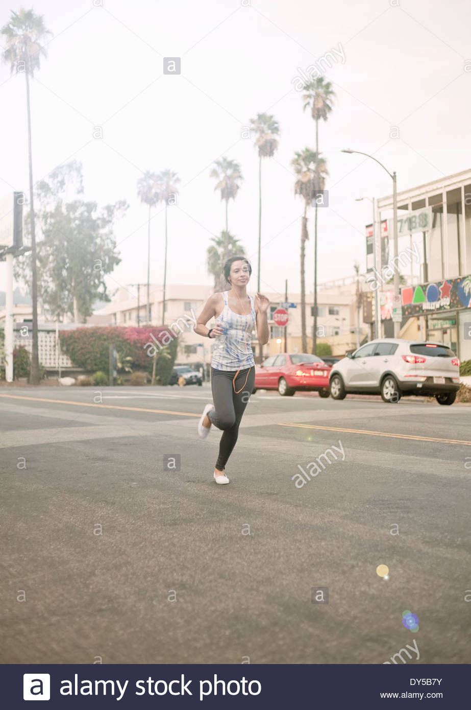 Young athletic woman running on road - Stock Image