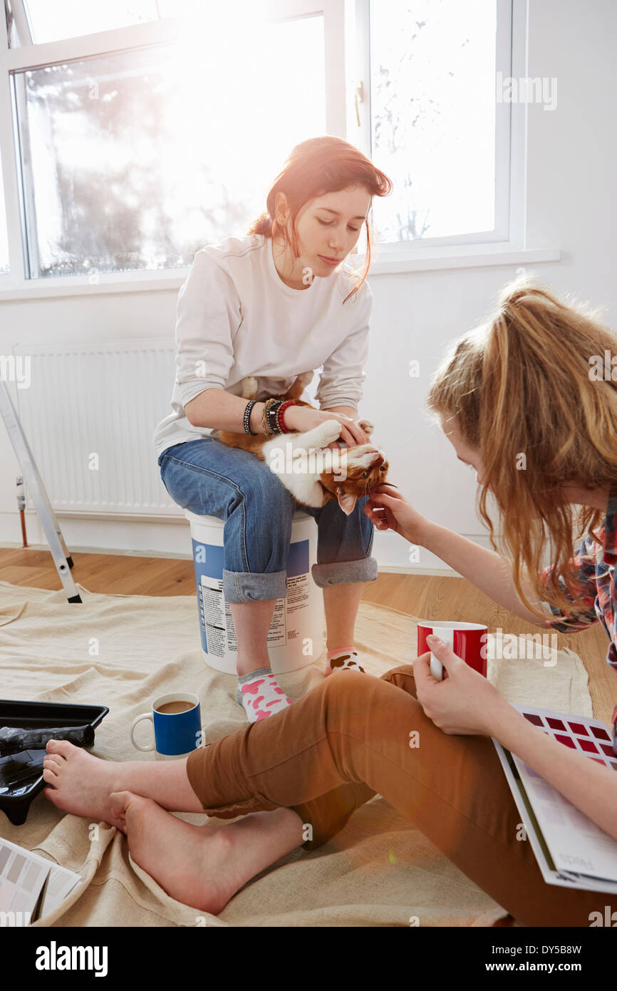Two teenage sisters with color swatches, coffee and a cat - Stock Image