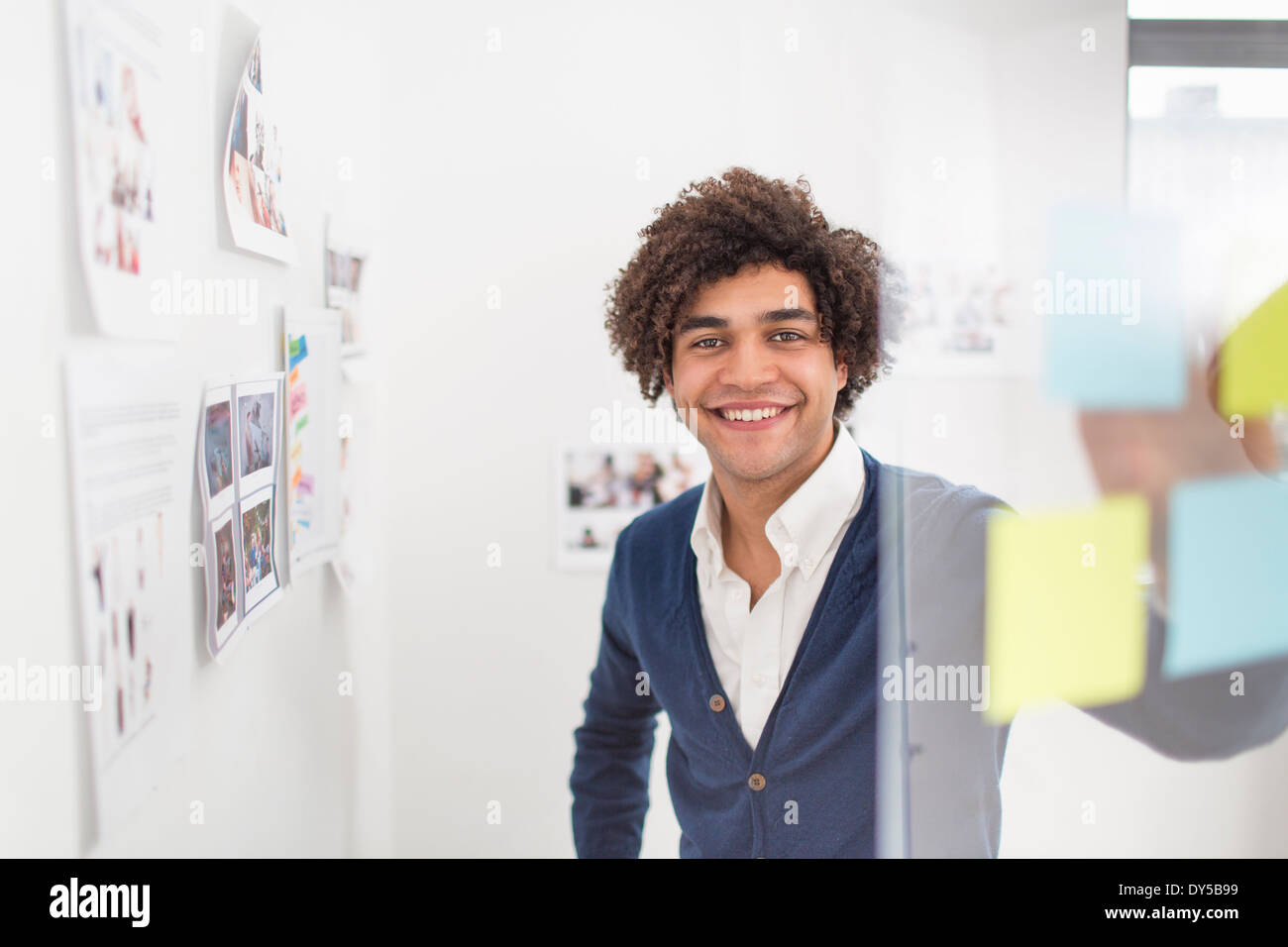 Young man with adhesive notes, smiling - Stock Image