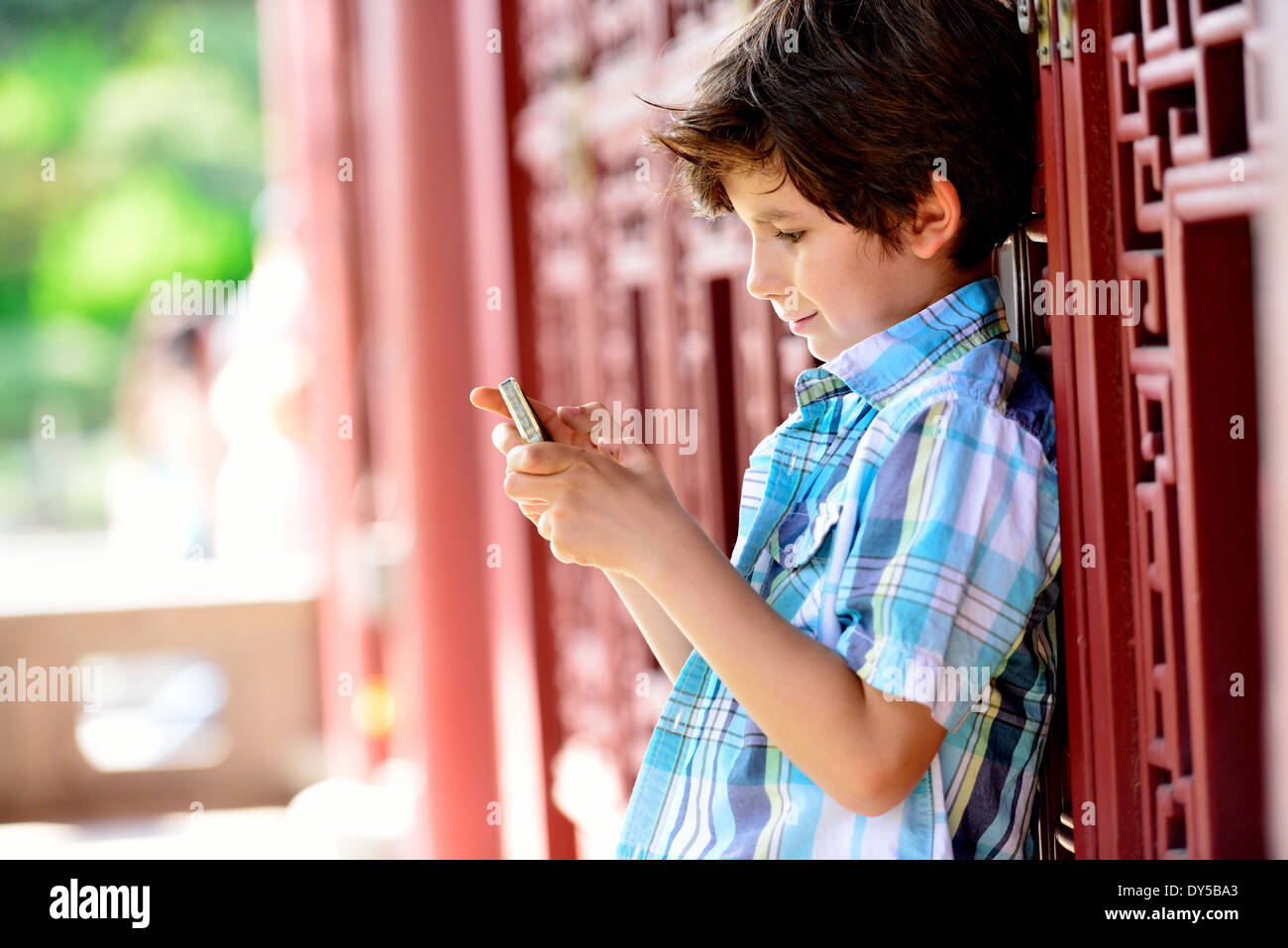 Boy leaning against red door texting on cellphone - Stock Image