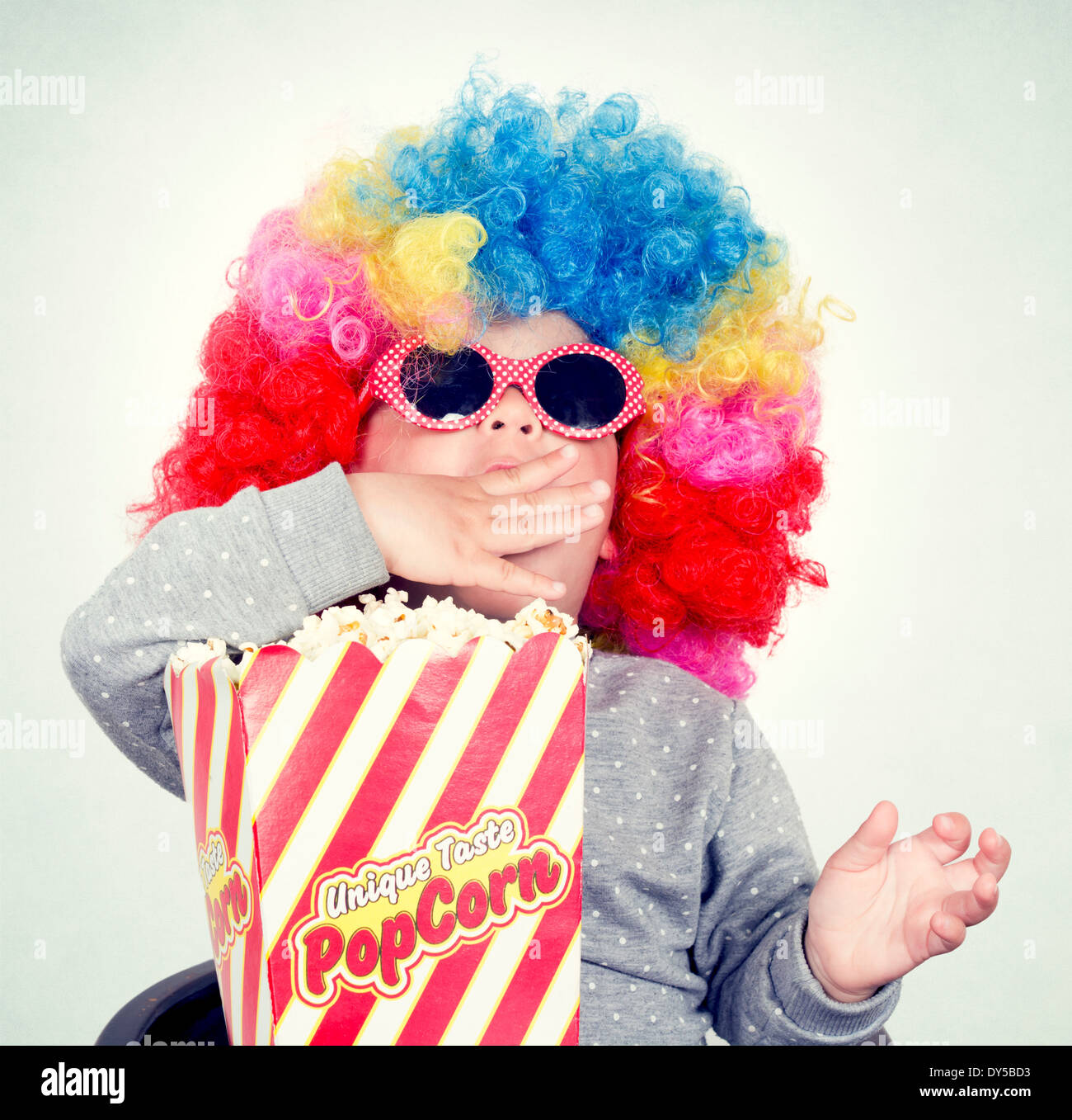 Child with clown wig and sunglasses eating pop corn - Stock Image