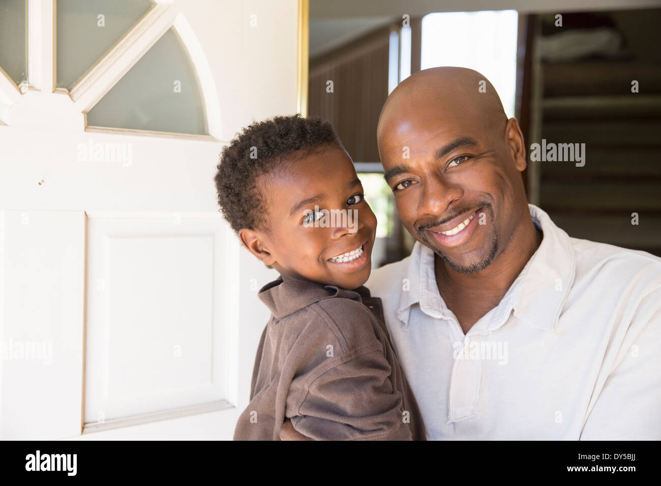 Portrait of mature man and son at front door - Stock Image