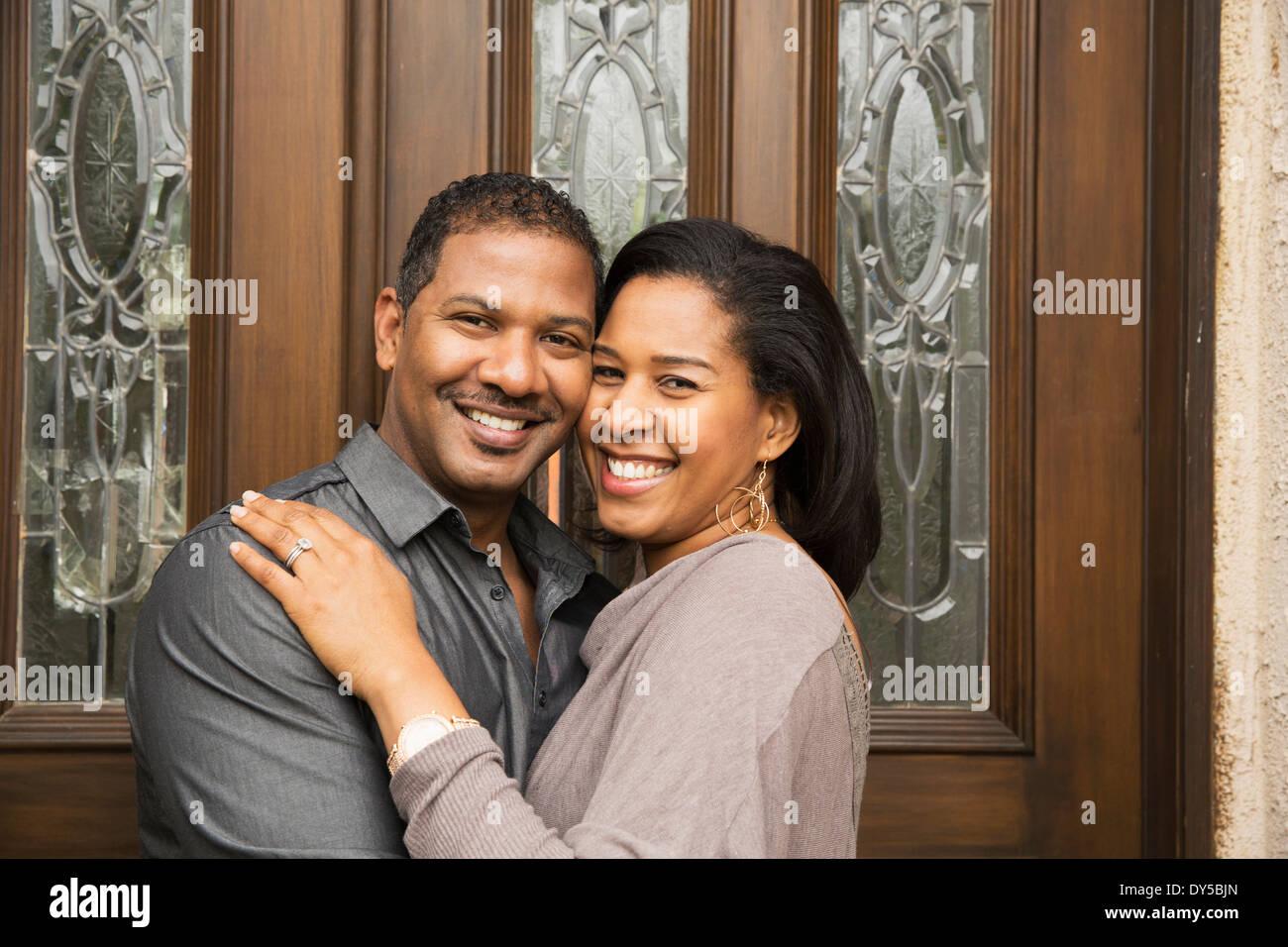 Portrait of happy mid adult couple at front door - Stock Image