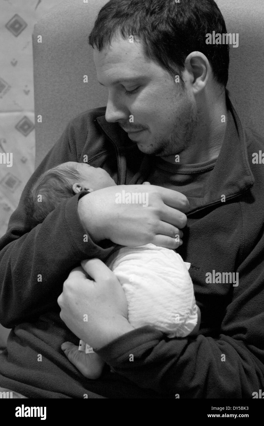 Black and white shot of a father holding and looking adoringly at his newborn baby girl - Stock Image