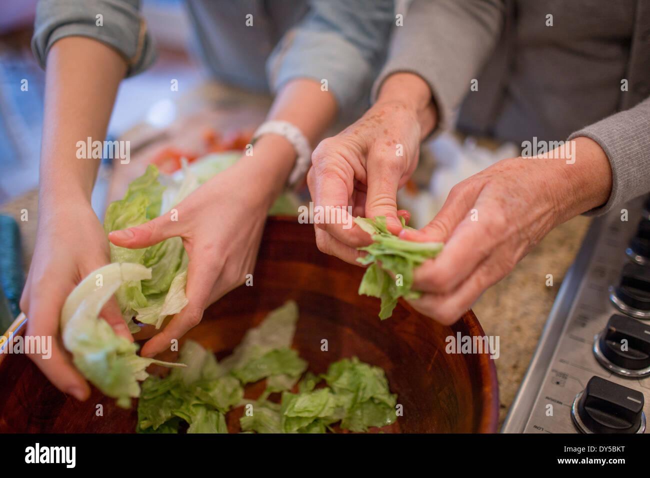 Senior woman and granddaughter preparing lettuce for salad - Stock Image