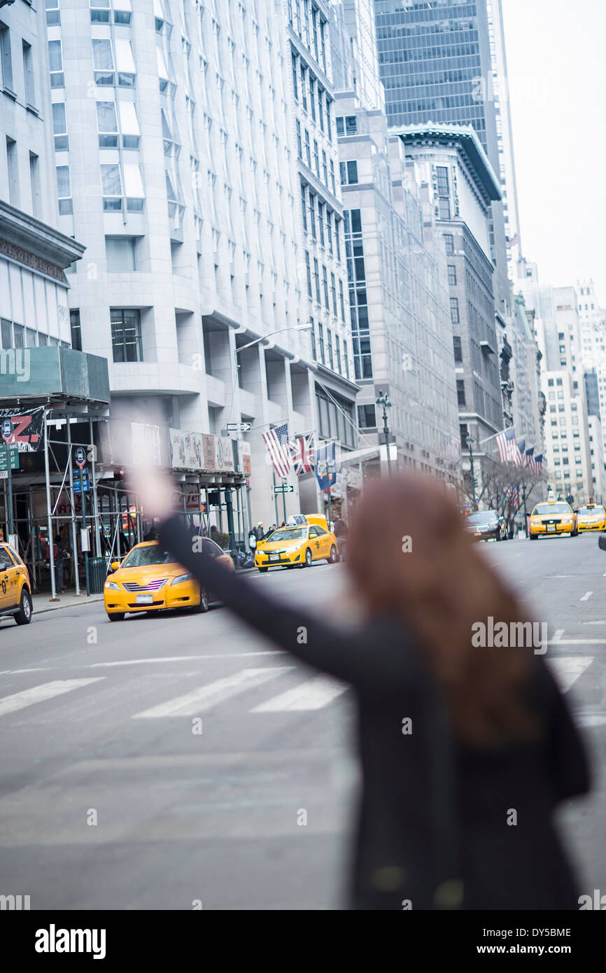 Young woman hailing a yellow cab, New York, USA - Stock Image