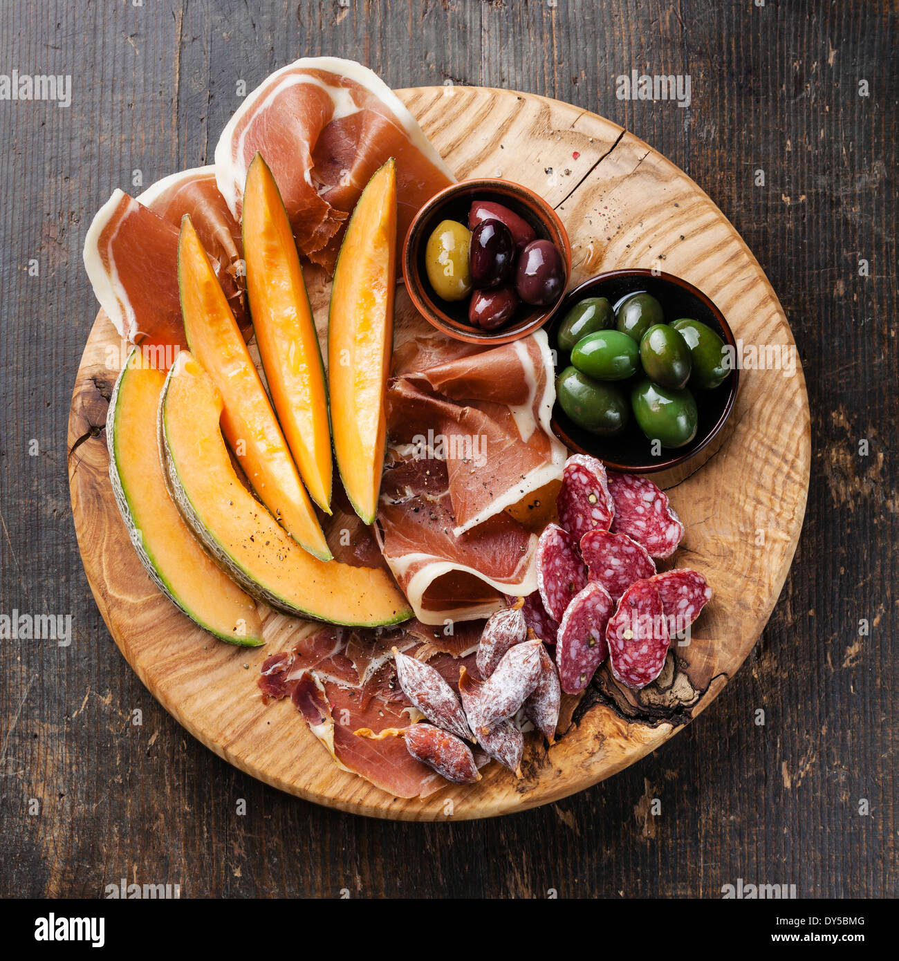 Antipasto ham, melon and olives on wooden background - Stock Image