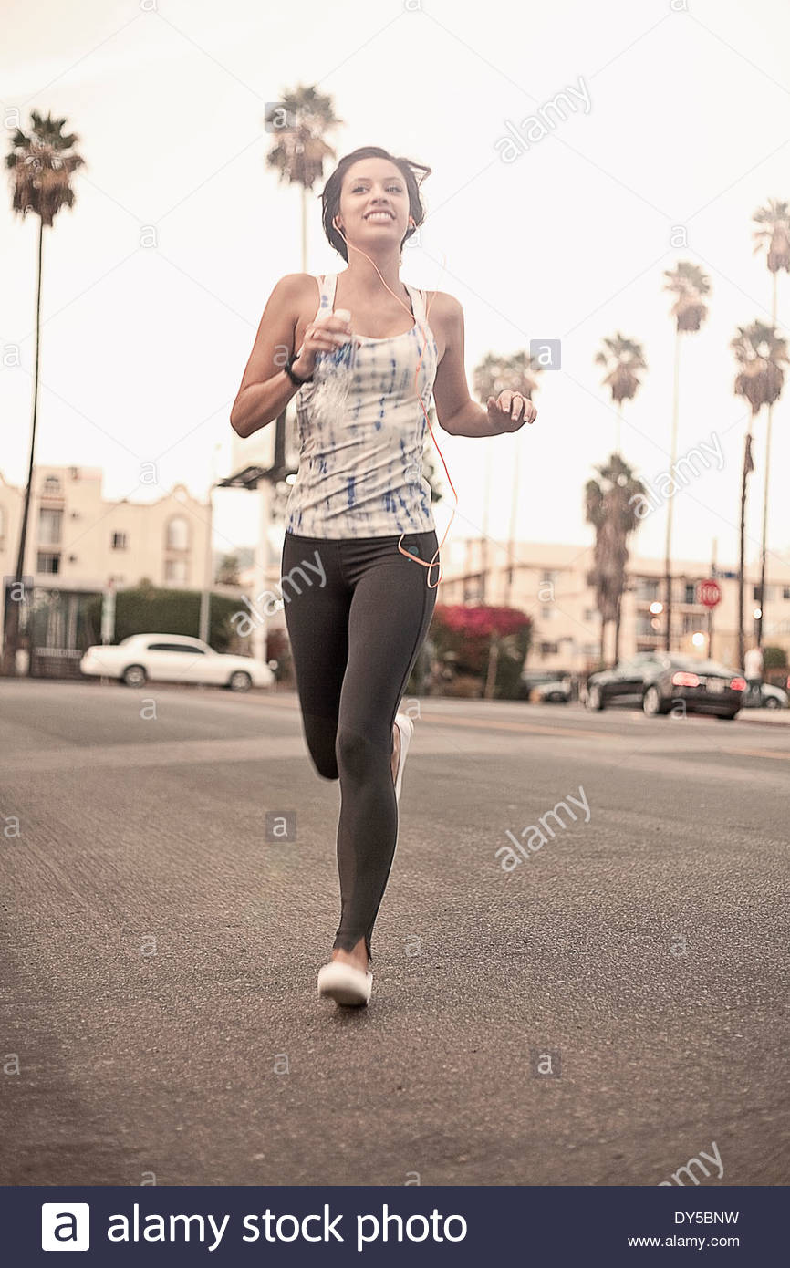 Young athletic woman running and listening to earphones - Stock Image