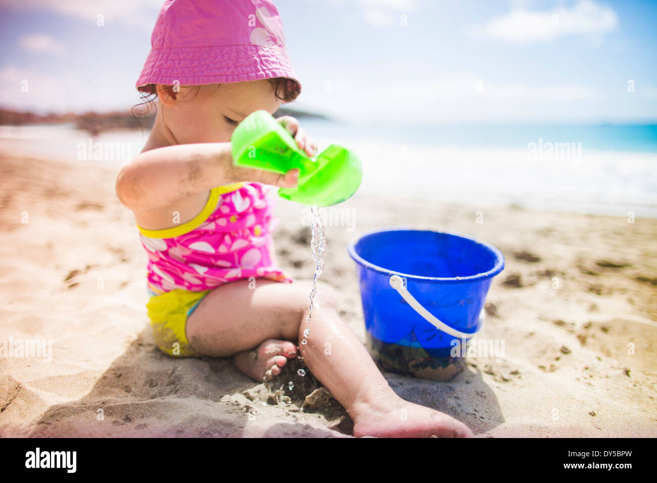Baby playing on sandy beach with bucket and spade - Stock Image