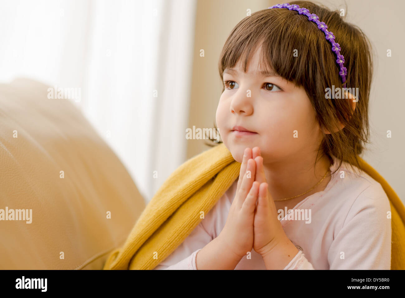 Young girl sitting on sofa daydreaming - Stock Image