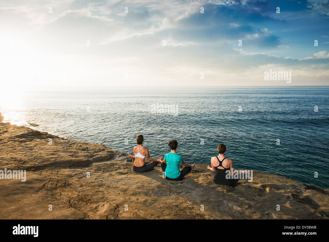 Women sitting on cliff top, looking at sea and meditating Stock Photo