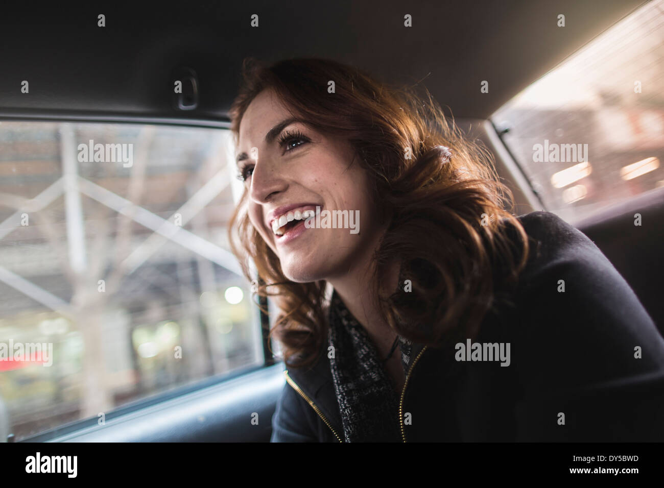 Happy young woman in back seat of taxi - Stock Image