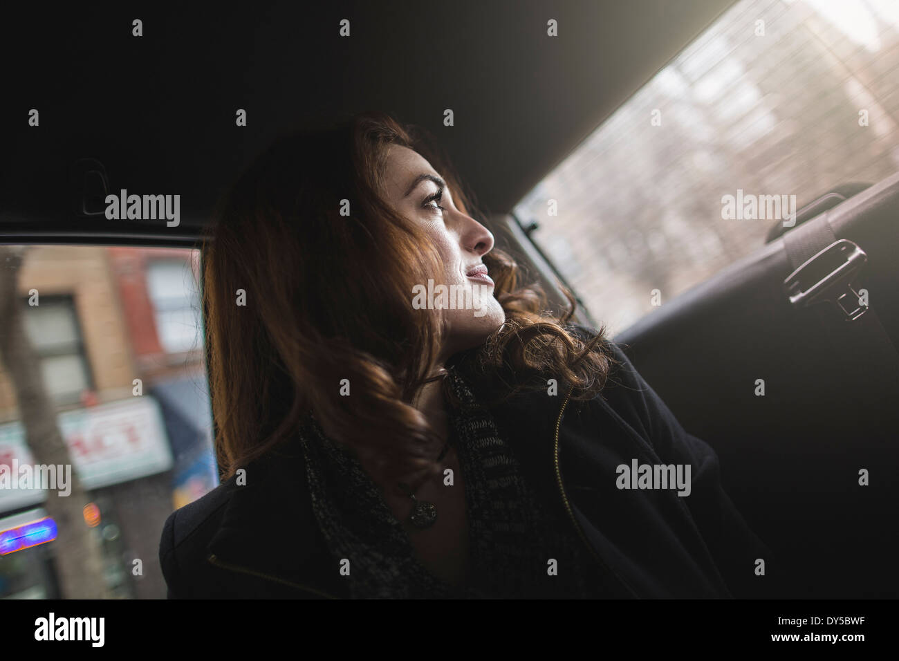 Young woman looking over her shoulder from taxi - Stock Image