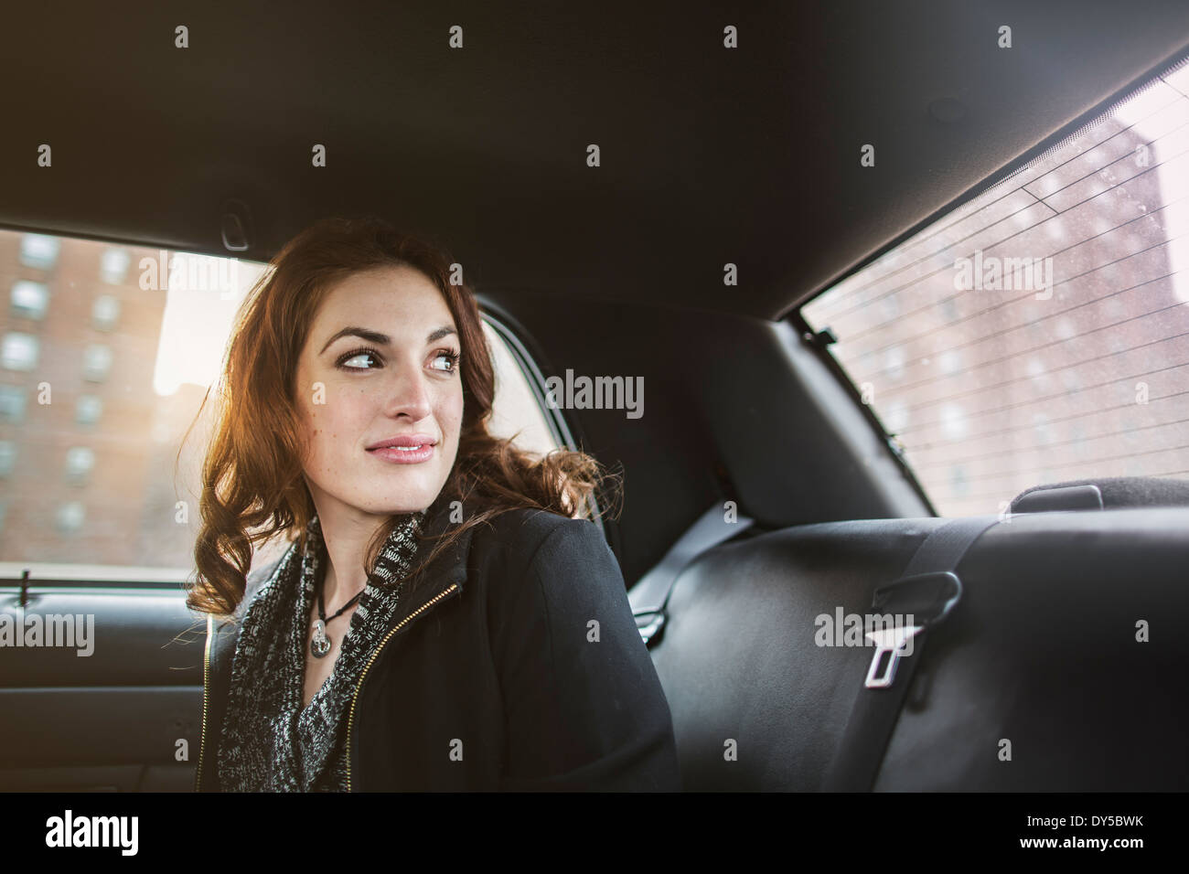 Young woman looking back from taxi - Stock Image