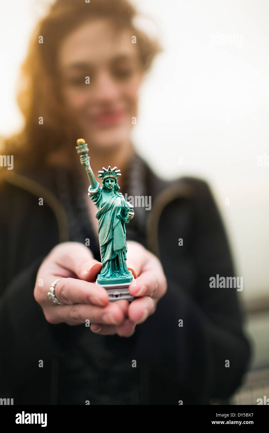 Young woman holding statue of liberty souvenir by Hudson river, New York, USA - Stock Image