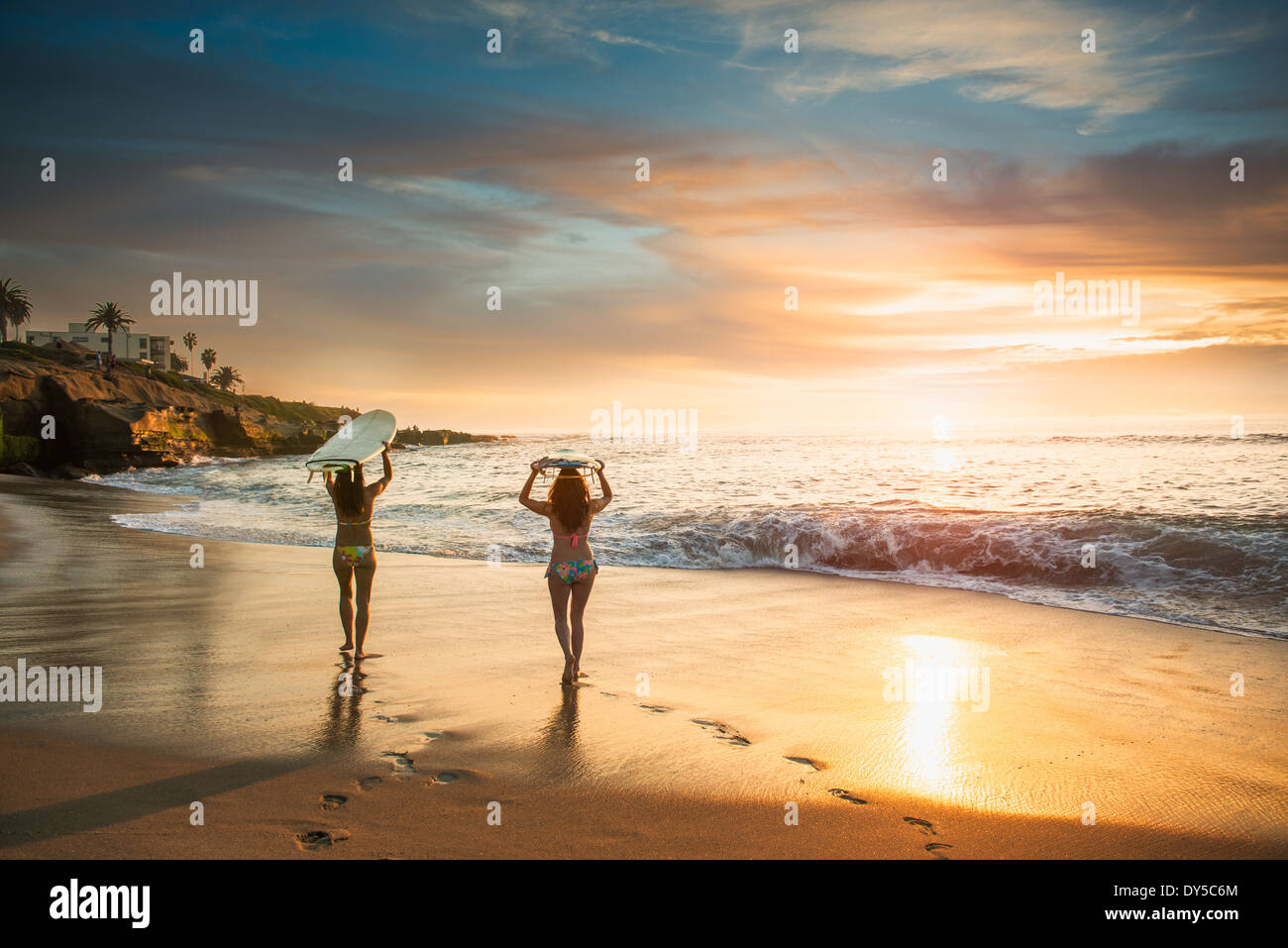 Surfers carrying surf board, walking along beach - Stock Image