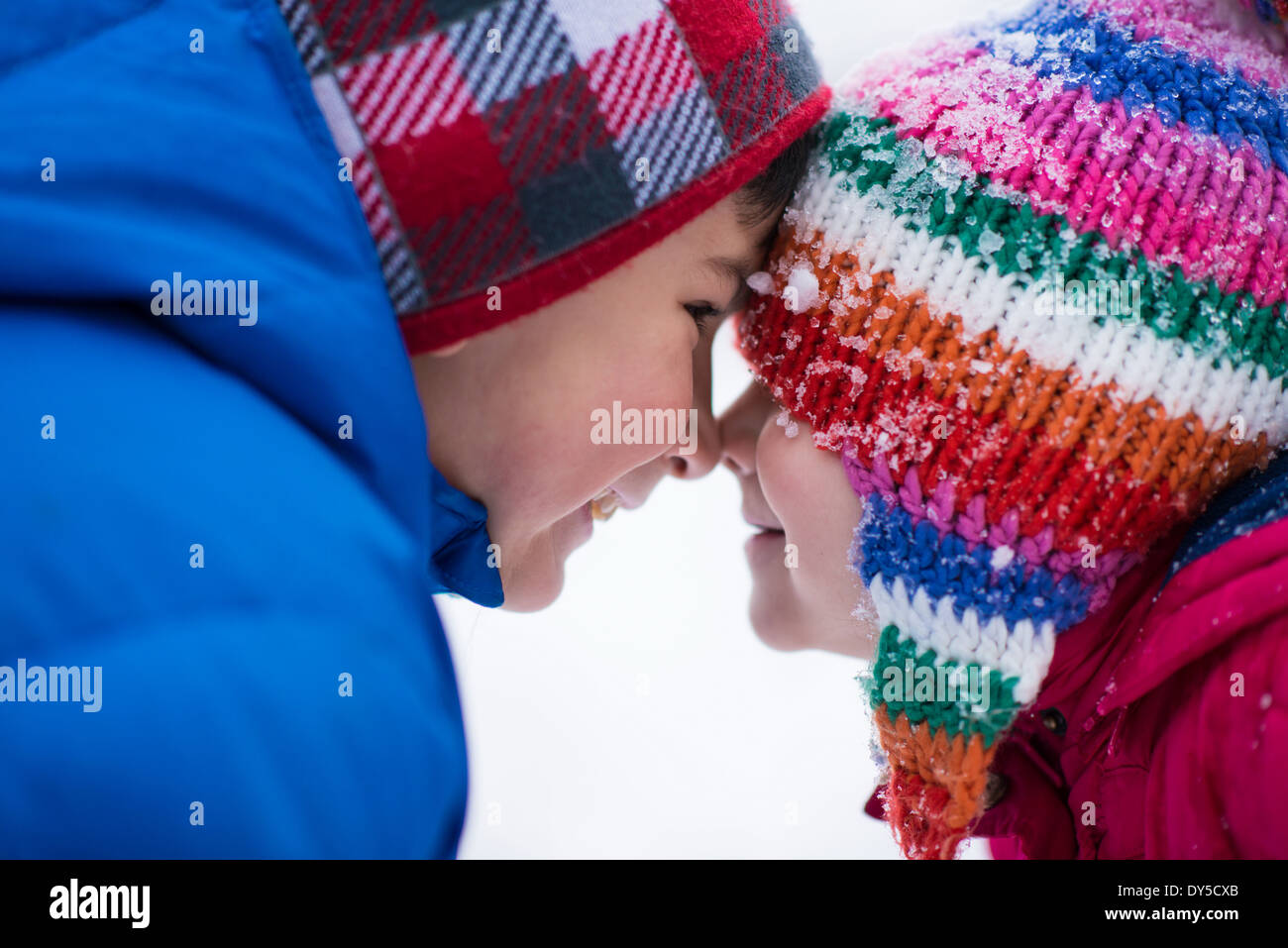 Brother and sister face to face in snow - Stock Image
