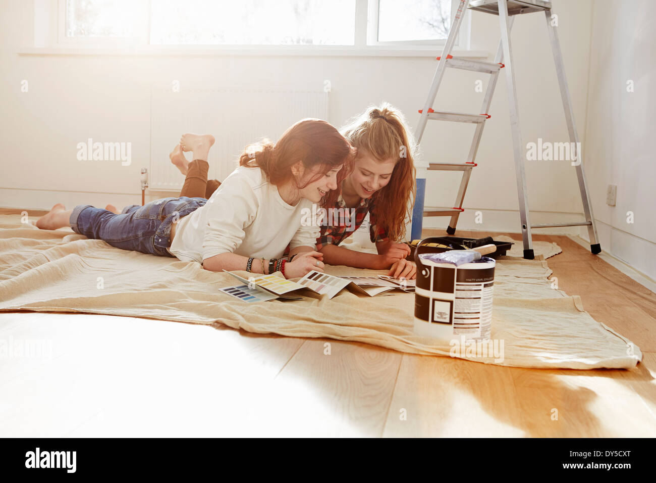 Two teenage sisters lying on floor looking at color swatches - Stock Image