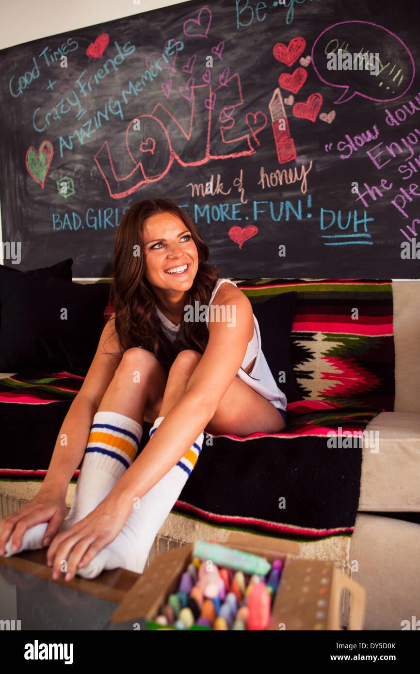 Young woman sitting on sofa wearing socks - Stock Image