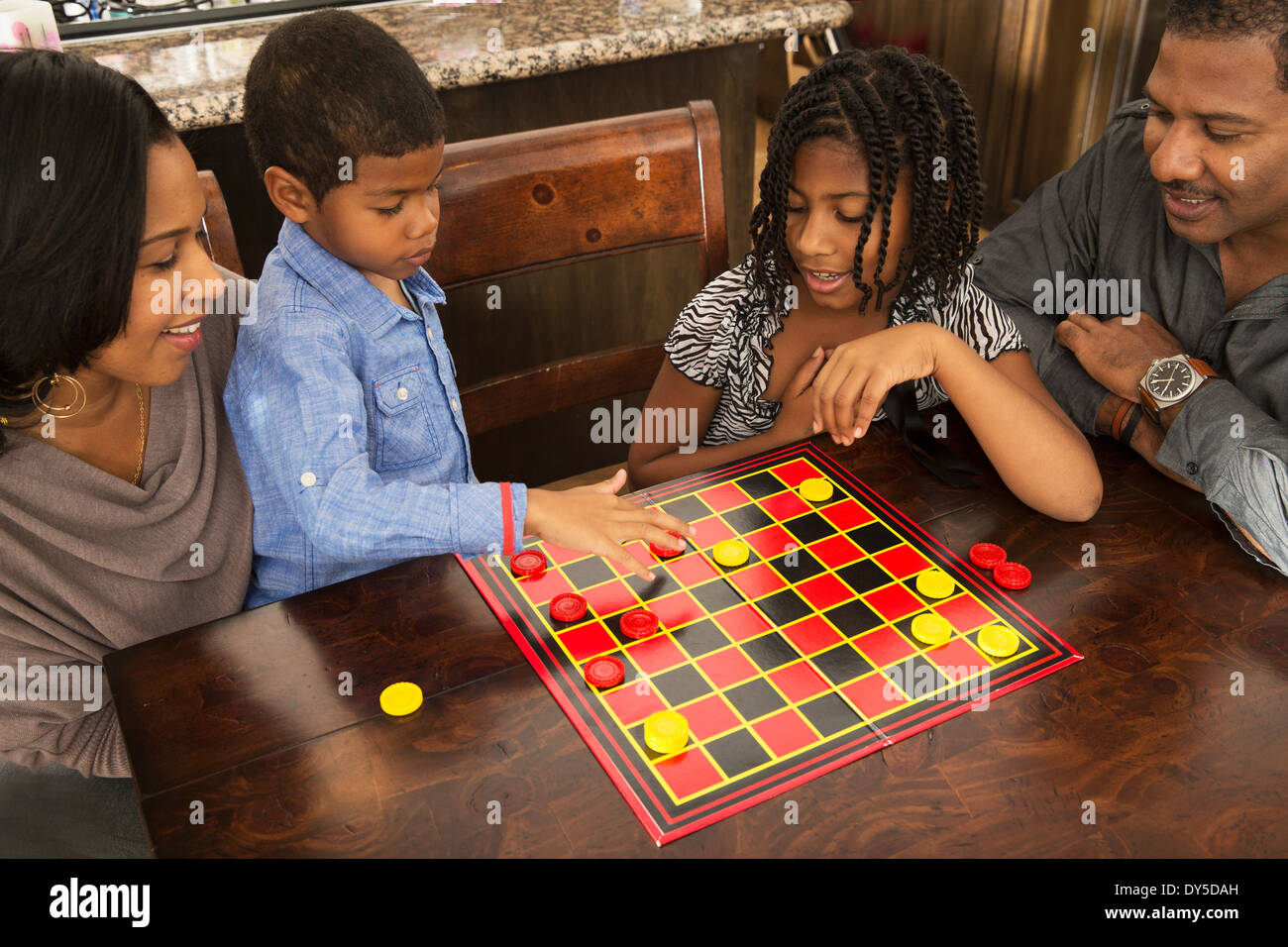 Mid adult couple and children playing draughts at dining table - Stock Image