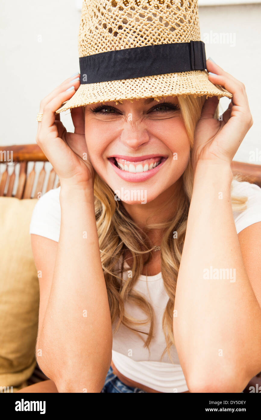 Young woman putting on straw hat Stock Photo
