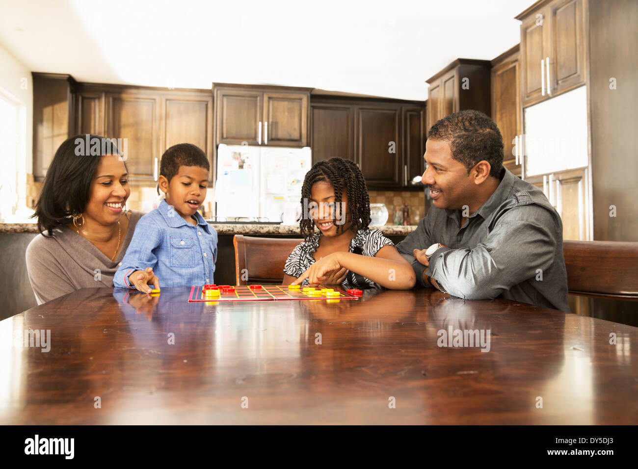 Mid adult couple and children playing draughts at table - Stock Image