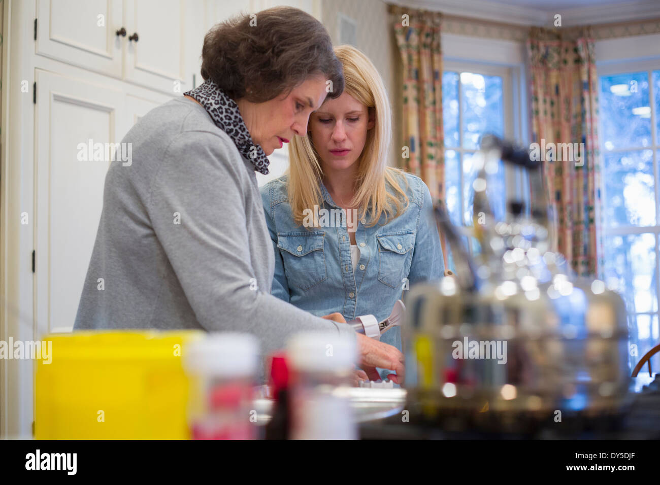 Senior woman and granddaughter baking together - Stock Image