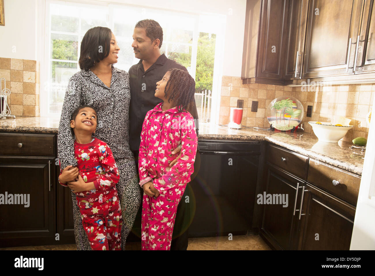 Mid adult couple with son and daughter in kitchen - Stock Image