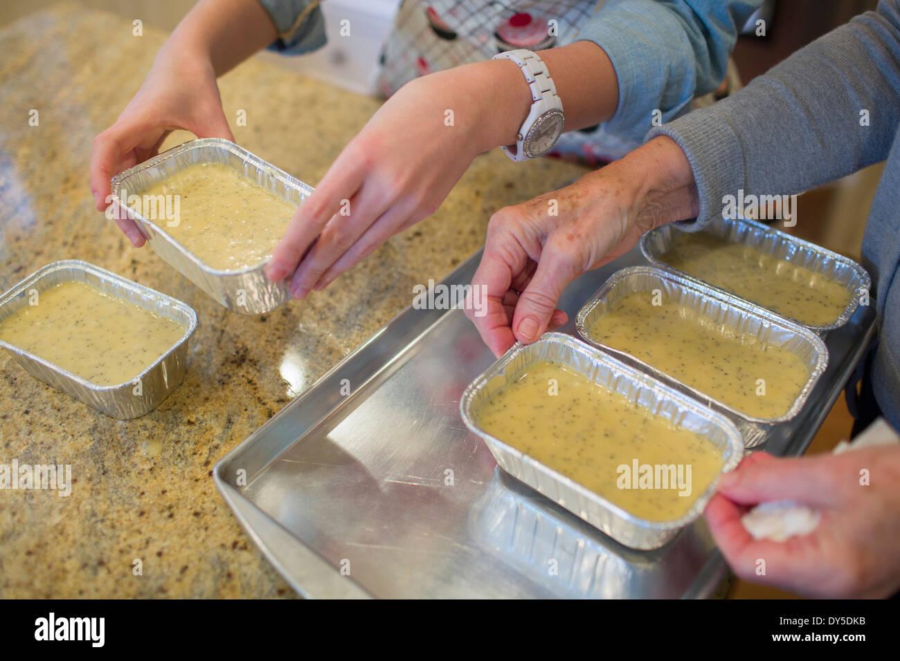 Senior woman and granddaughter preparing baking tins - Stock Image