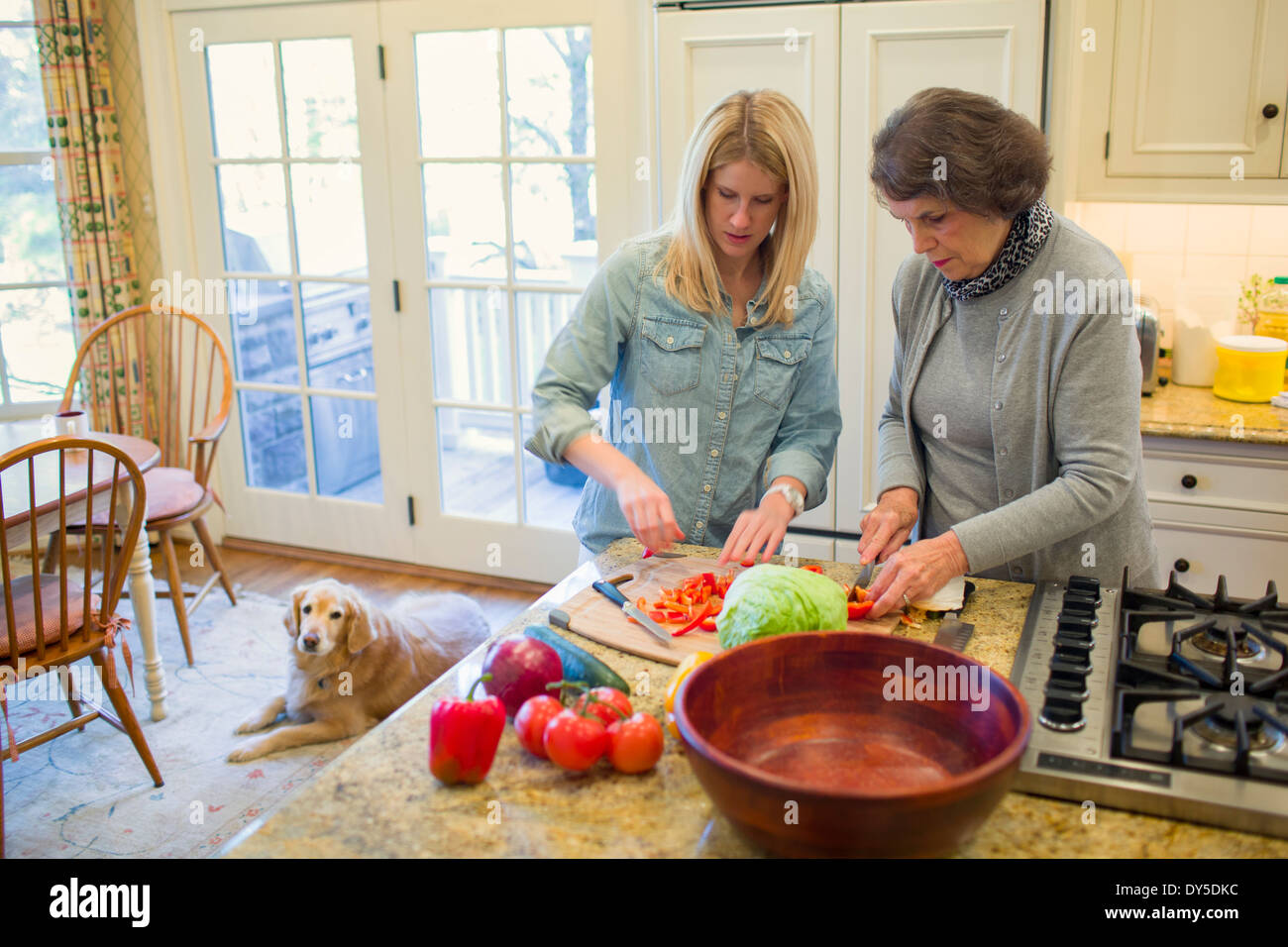 Senior woman and granddaughter chopping vegetables for salad bowl - Stock Image