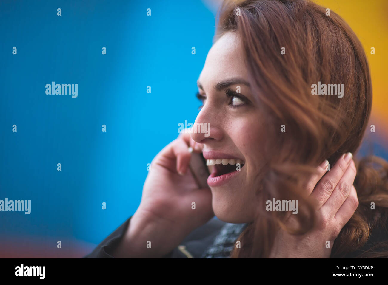 Young businesswoman talking on cellphone on city street - Stock Image