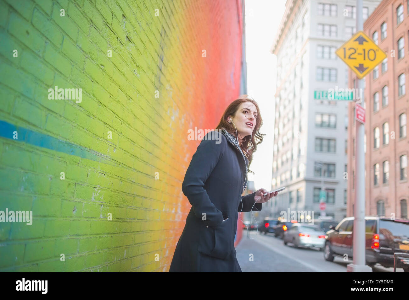 Young woman waiting on city street - Stock Image