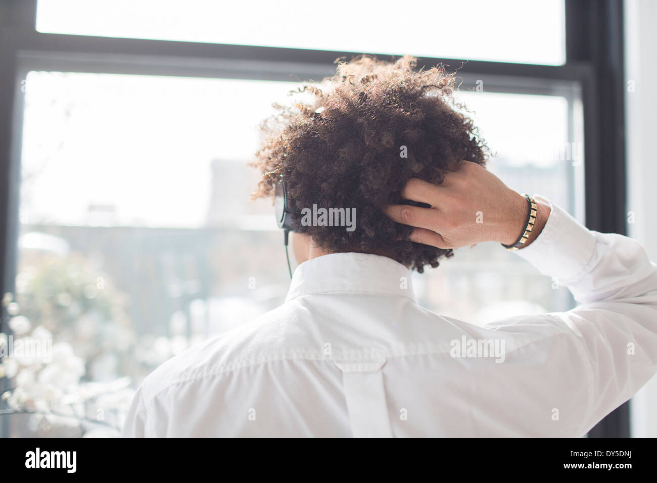 Young man scratching head, rear view - Stock Image