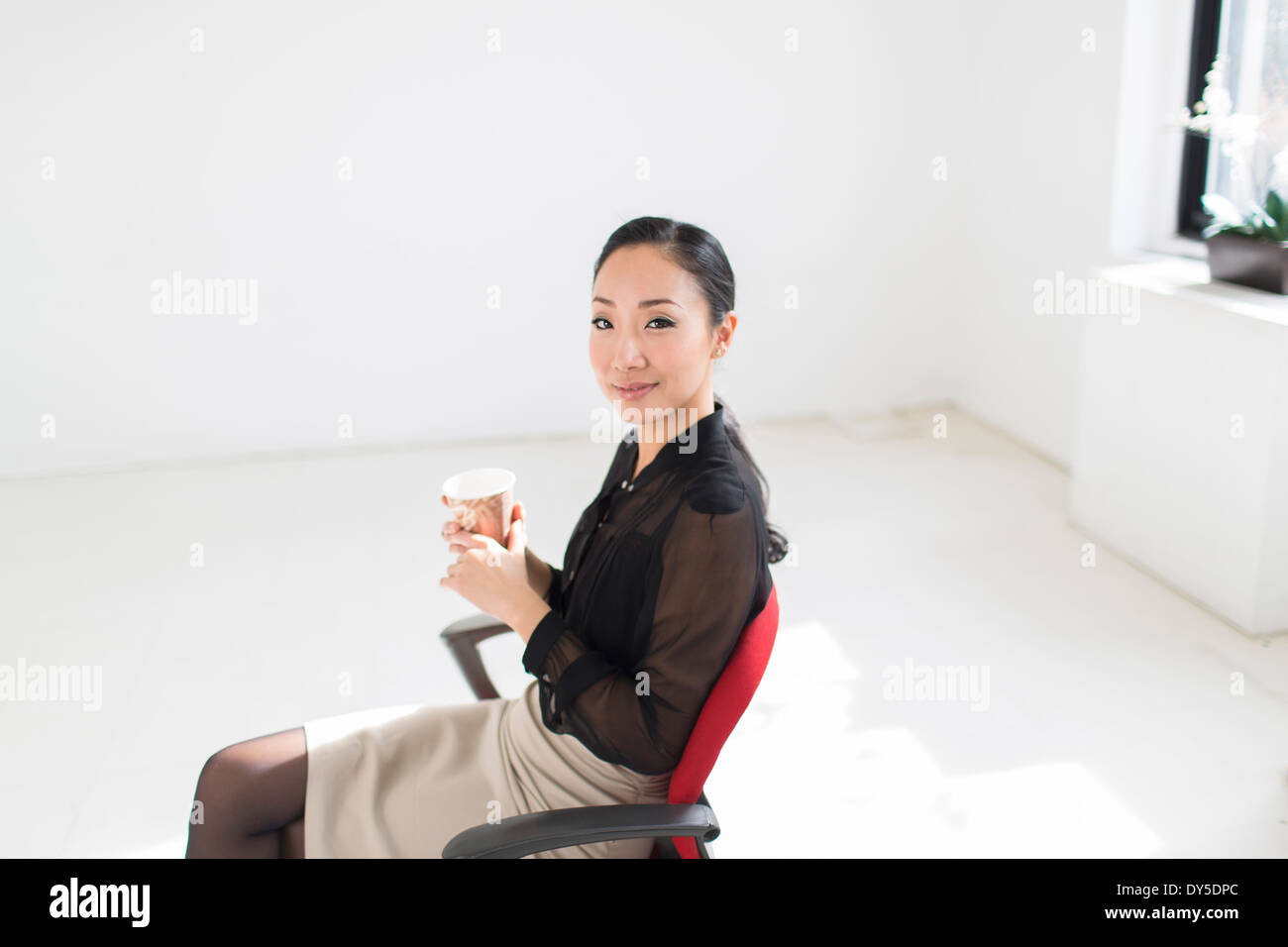 Young woman sitting on office chair with coffee - Stock Image