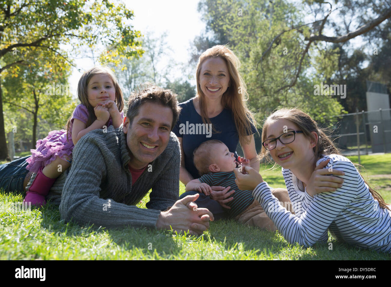 Happy family relaxing on grass - Stock Image