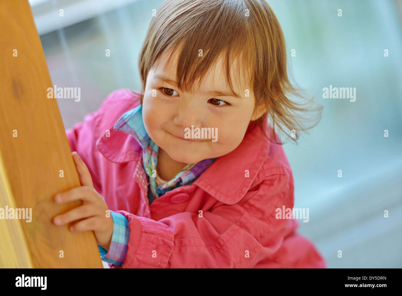 Female toddler peeking from a wooden post - Stock Image
