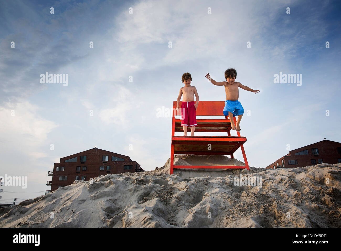 Two boys jumping off red notice board, Long Beach, New York State, USA - Stock Image