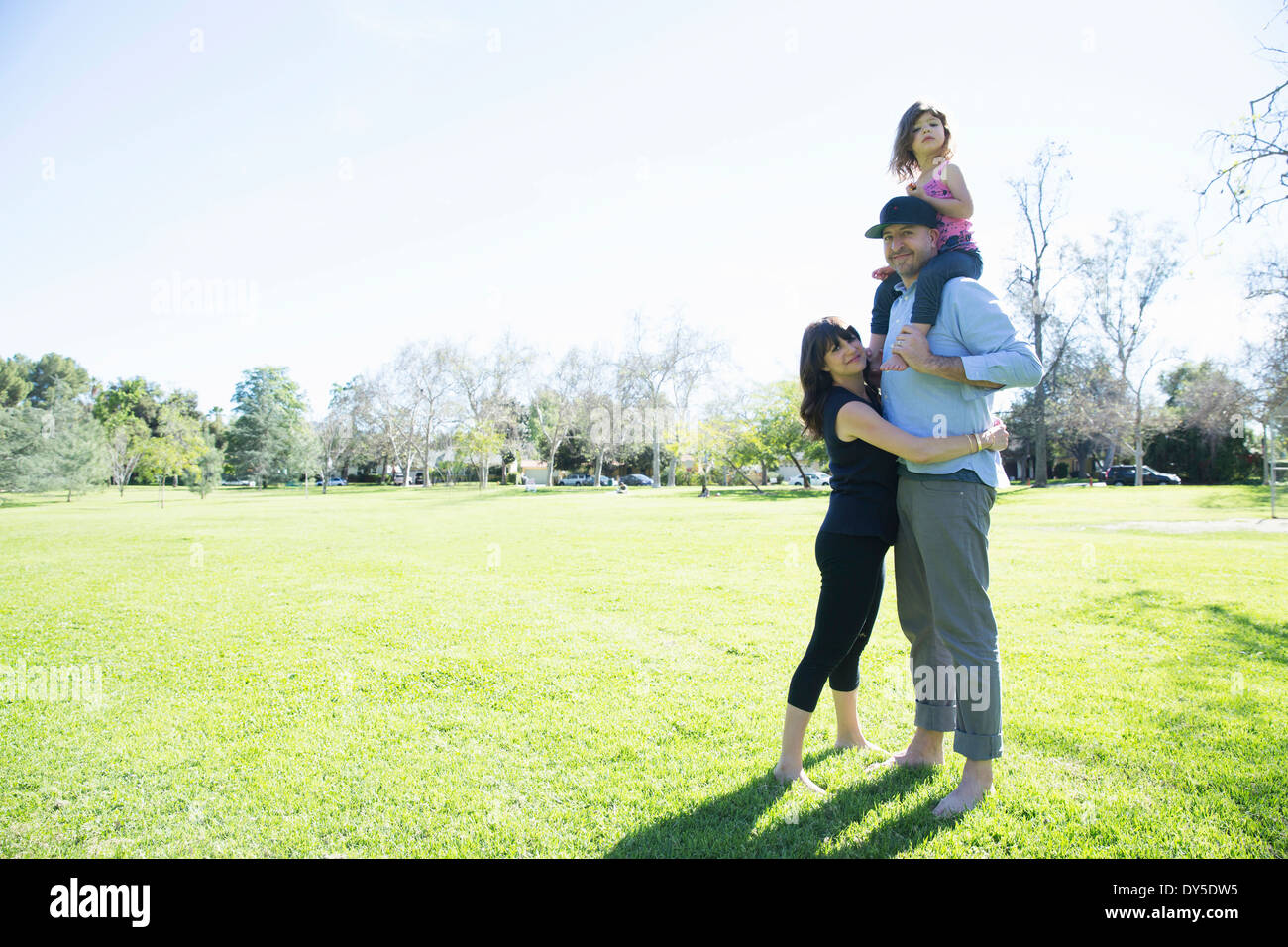 Mid adult couple enjoying the park with young daughter - Stock Image
