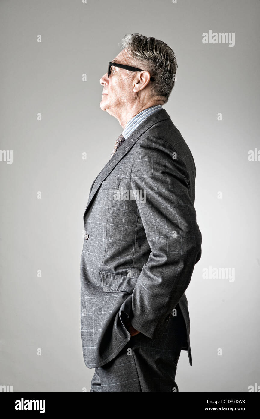 Portrait of senior man, wearing suit, side view - Stock Image