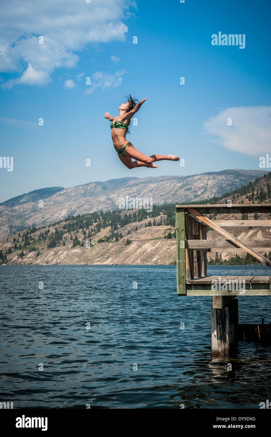 Young woman jumping into Okanagan Lake, Naramata, British Columbia, Canada - Stock Image