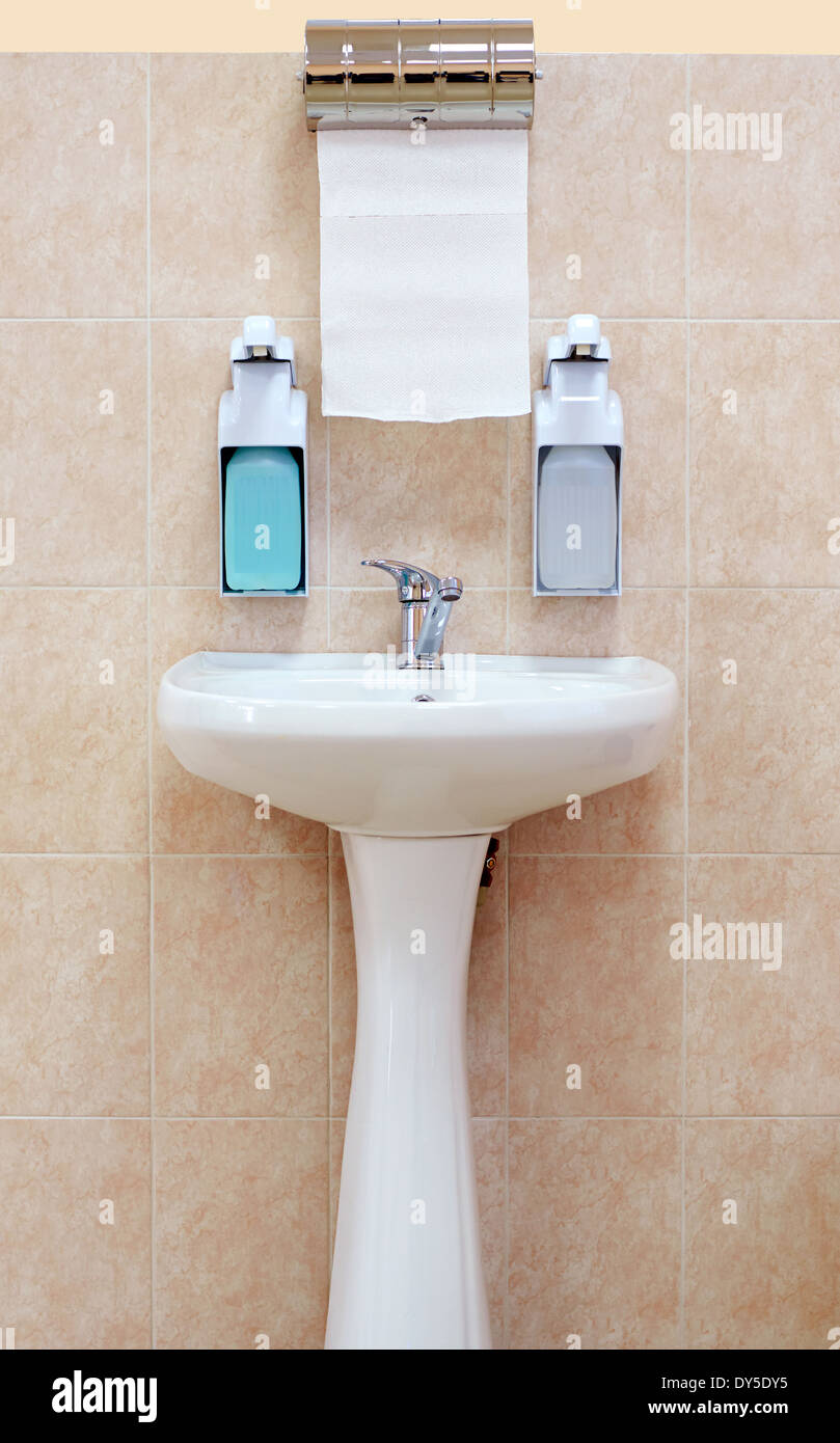Washbasin with a paper towel and liquid soap on the background wall of brown tiles - Stock Image