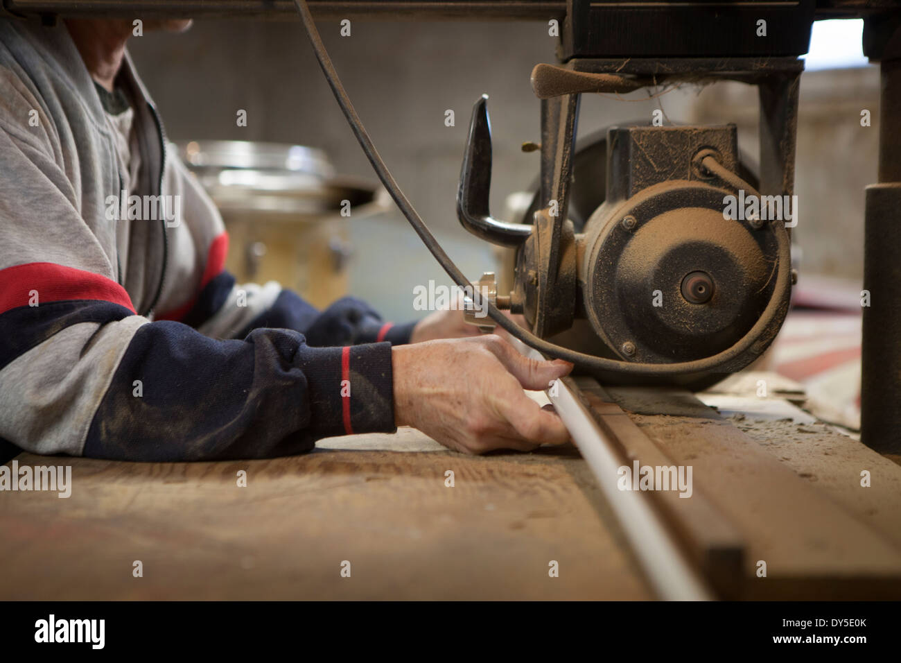 Close up of man using radial arm saw in workshop - Stock Image