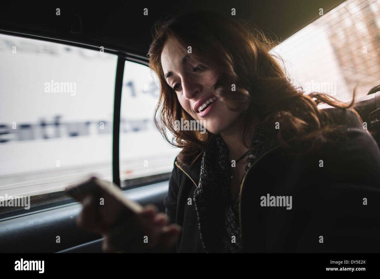 Young woman looking at cellphone in taxi - Stock Image