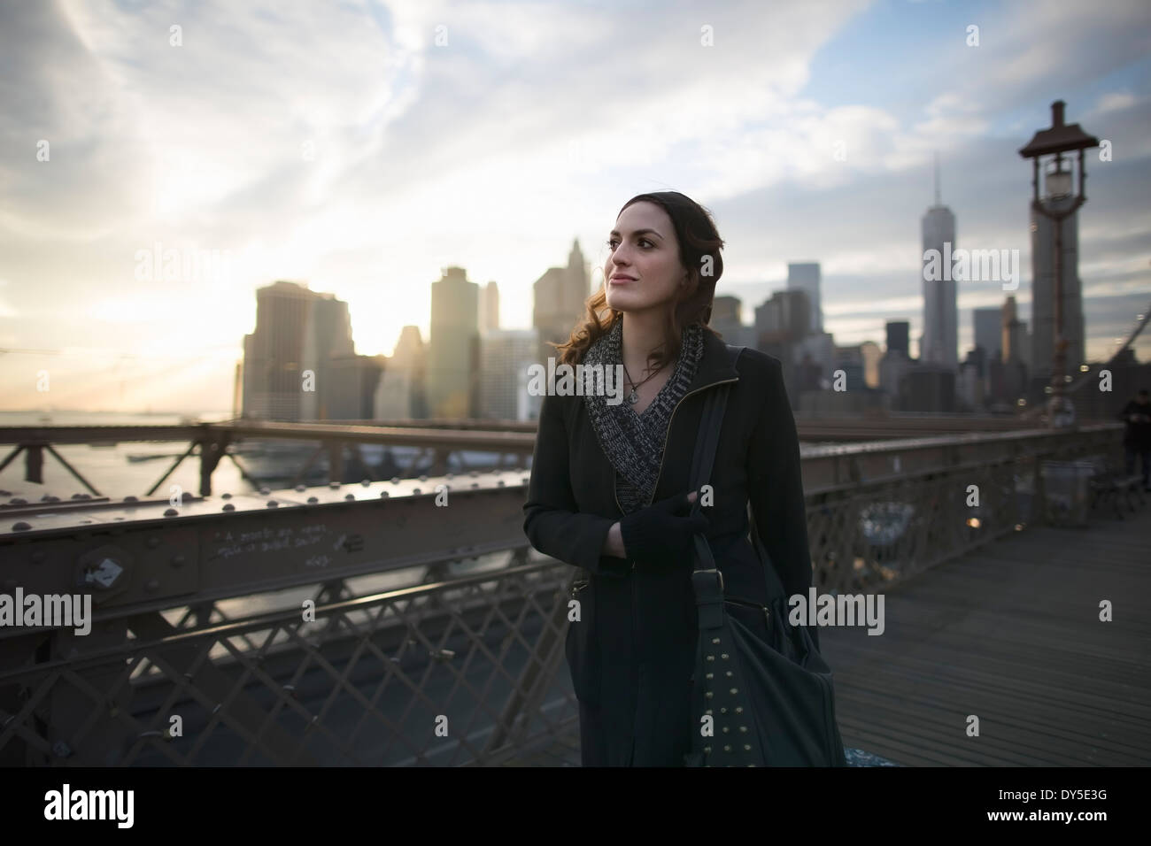 Young woman strolling on Brooklyn bridge, New York, USA - Stock Image